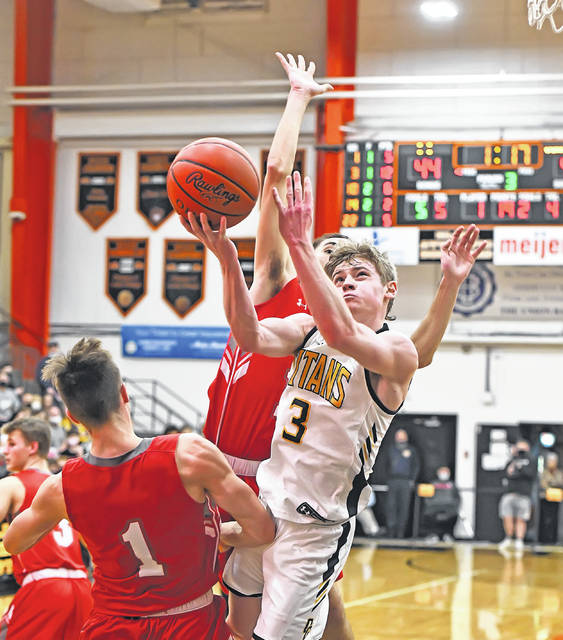 Ottawa-Glandorf's Brennen Blevins puts up a shot against Johnstown's Gavin Foe, left, and Brandon McConnell during Saturday night's Division III regional final at the Elida Fieldhouse.