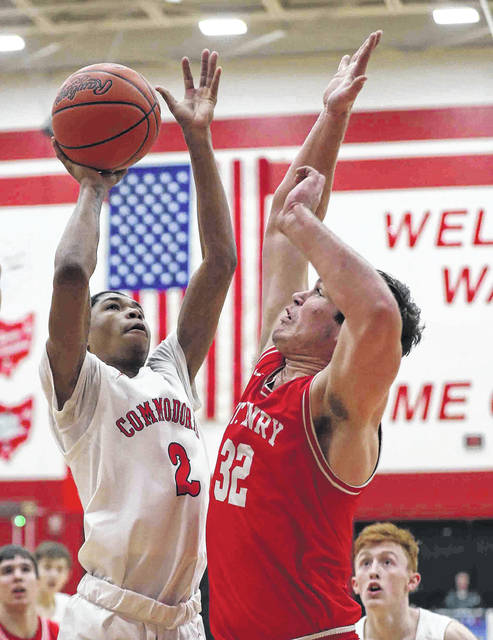 Perry's #2 Will Knight (2) puts up a shot against St. Henry's Logan Lefeld during a Tuesday night Division IV district semifinal at Wapakoneta.