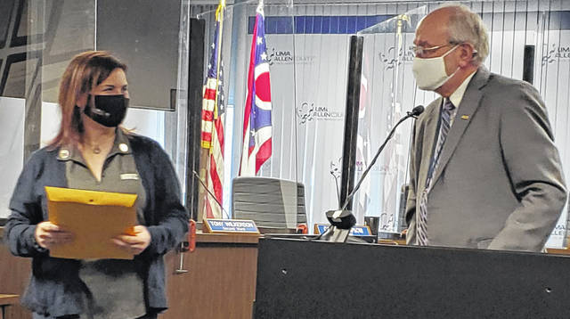 Anne Pfleger, left, the president of National Association of Women in Construction, accepts a proclamation for Women in Construction Week from Lima Mayor David Berger on Wednesday.