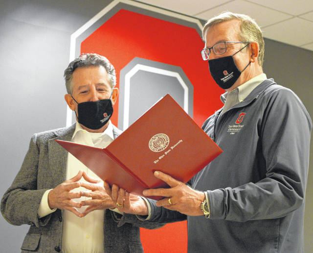 Dr. David Rolsten (left) is presented with a signed endowment document for the David Rolsten First Generation Endowed Fund by Ohio State University at Lima dean and director Tim Rehner, Saturday at the Lima campus.
