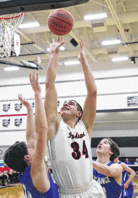 Shawnee's Tyson Elwer (34) puts up a shot against Defiance's Isaac Schlatter, left, and CJ Zachrich during a Wednesday night Division II district semifinal at Spencerville.