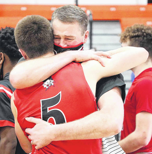 Assistant coach Nick Bertke hugs his son, Jarin, after Shawnee defeated Akron Buchtel in Saturday's Division II regional final at the Elida Fieldhouse.