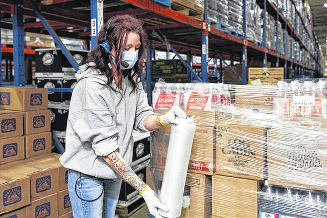 An employee of SpartanNash's Grand Rapids, Mich., Distribution Center wraps a pallet with plastic wrap while wearing personal protective equipment, one of the changes made by the company. SpartanNash has a similar distribution center on Lima's east side.
