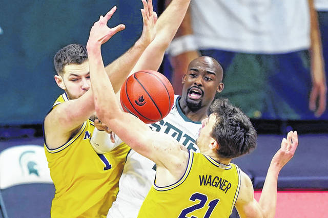 Michigan State guard Joshua Langford (1) passes as Michigan center Hunter Dickinson (1) and guard Franz Wagner (21) defend during the Spartans' 70-64 win over the Wolverines on Sunday in the Breslin Center.