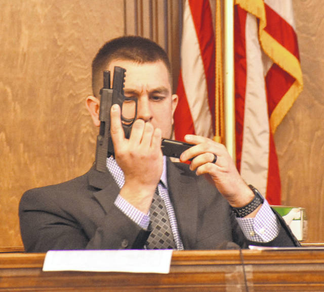 Sgt. Brandon Hemker of the Allen County Sheriff's Office displays for jurors a Sig Sauer P250 .40 caliber firearm that was found at the home of Jaishaun Ball during an April 1 raid by a local task force.