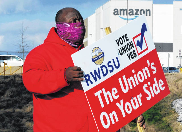 Michael Foster of the Retail, Wholesale and Department Store Union holds a sign outside an Amazon facility where labor is trying to organize workers in Bessemer, Ala.