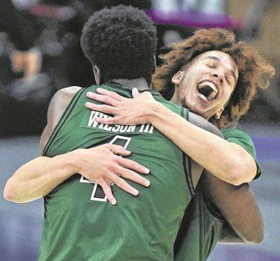 Ohio's Jason Preston, right, celebrates with teammate Dwight Wilson III after the Bobcats defeated Buffalo in the Mid-American Conference tournament championship game Saturday in Cleveland.