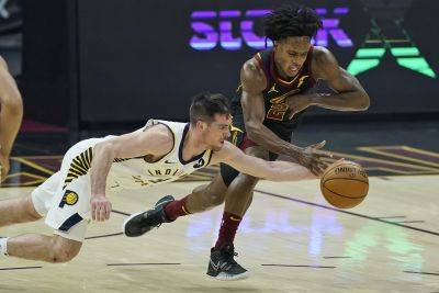 Indiana Pacers' T.J. McConnell, left, and Cleveland Cavaliers' Collin Sexton reach for the ball during Wednesday night's game in Cleveland. (AP photo)