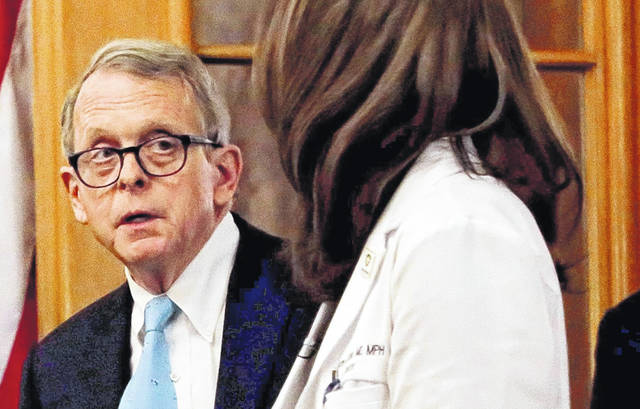 Ohio Gov. Mike DeWine and then-Ohio Department of Health director Dr. Amy Acton prepare for an update on the state's response to COVID-19 one year ago this month.