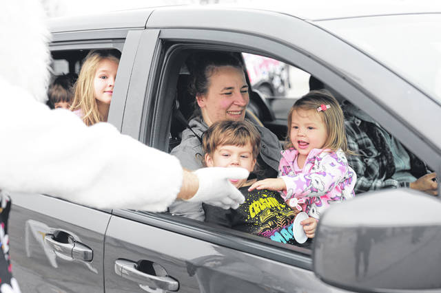 The Pietrzyk family gives the bunny a high-five during the 4H Easter Egg Drive Thru at the Allen County Fairgrounds on Saturday morning.