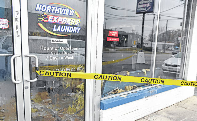 Northview Express Laundry's owner looks over the debris after a fire started at the laundromat, 138. W. Grand Ave., Lima, late Tuesday night.