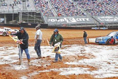 Safety workers spread drying agent before heat races for a NASCAR Truck Series race Saturday in Bristol, Tenn. (AP photo)