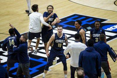 Oral Roberts players and coaches celebrate after beating Ohio State in the NCAA Tournament on Friday at Mackey Arena in West Lafayette, Ind. (AP Photo)