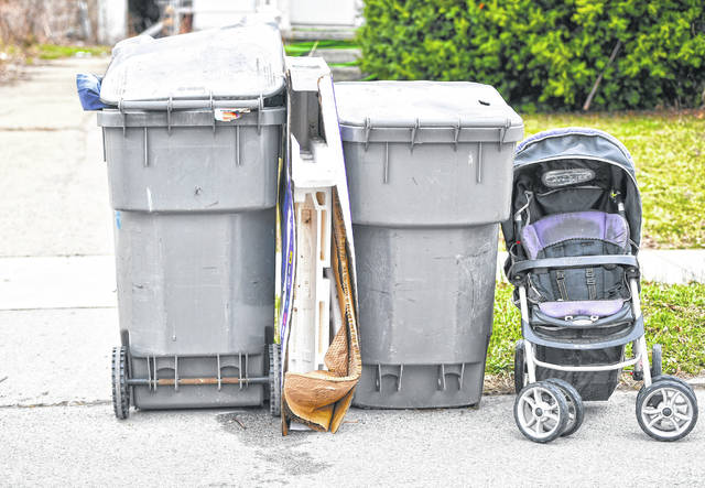 Refuse bins sit by a curb Thursday afternoon in Lima.