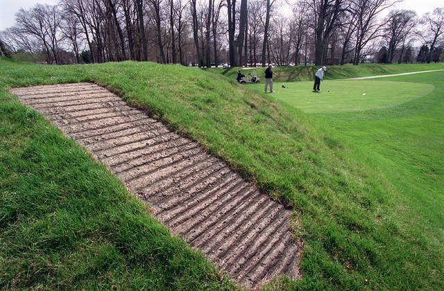 This April 6, 2000, file photo shows a concrete walkway, foreground, that allows golfers access to the top of an ancient American Indian mound at Moundbuilders Country Club in Newark. The Ohio Supreme Court heard oral arguments Tuesday in the debate over public access to the set of ancient ceremonial and burial earthworks. The case pits the state historical society against the country club where the earthworks are located.