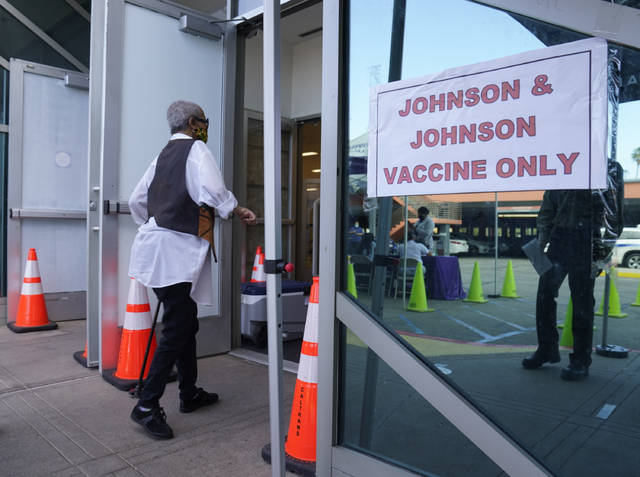 """FILE - In this April 1, 2021 file photo, people walk in to get their COVID-19 vaccine at the Baldwin Hills Crenshaw Plaza in Los Angeles. The U.S. is recommending a """"pause"""" in administration of the single-dose Johnson & Johnson COVID-19 vaccine to investigate reports of potentially dangerous blood clots. In a joint statement Tuesday, the Centers for Disease Control and Prevention and the Food and Drug Administration said it was investigating clots in six women in the days after vaccination, in combination with reduced platelet counts.  (AP Photo/Damian Dovarganes)"""