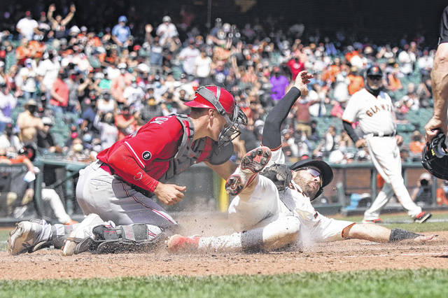 Cincinnati Reds catcher Tyler Stephenson, left, tags out San Francisco Giants' Curt Casali at home during the fifth inning of a baseball game in San Francisco, Wednesday, April 14, 2021. (AP Photo/Jeff Chiu)