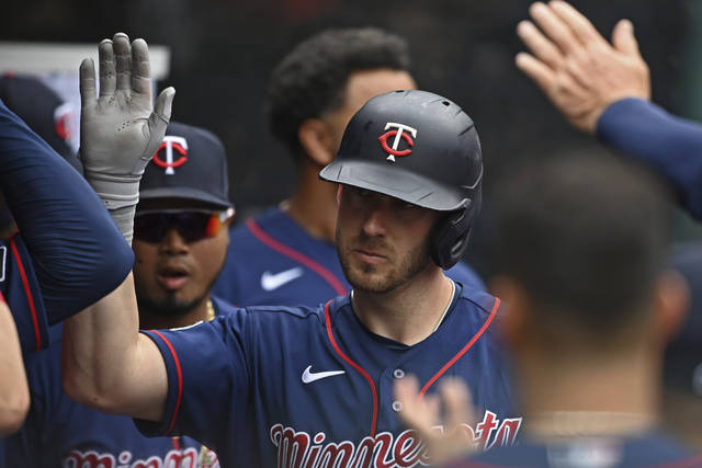 Minnesota Twins' Mitch Garver is congratulated in the dugout after hitting a solo home run off Cleveland Indians relief pitcher Sam Hentges in the fifth inning of a baseball game, Wednesday, April 28, 2021, in Cleveland. (AP Photo/David Dermer)