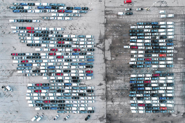 In this aerial photo, mid-sized pickup trucks and full-size vans are seen in a parking lot March 24 outside a General Motors assembly plant where they are produced in Wentzville, Mo. The global shortage of semiconductors is forcing General Motors to further cut production at six North American factories as chip supplies seem to be growing tighter. The shutdowns likely will crimp dealer inventory of vehicles made at the plants, but GM says it has managed to keep factories humming that make hot-selling and profitable full-size pickup trucks and SUVs.