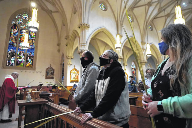 The Rev. William Schipper, left, pastor of Mary, Queen of the Rosary Parish, celebrates Palm Sunday Mass on March 28 as parishioners hold palm leaves at the Catholic church in Spencer, Mass. Parishioners wore masks out of concern for the coronavirus.