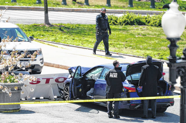U.S. Capitol Police officers stand near a car that crashed into a barrier Friday on Capitol Hill in Washington.
