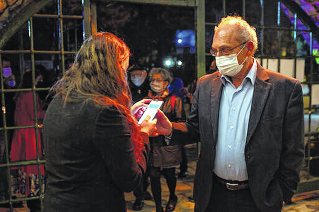 """A man presents his """"green passport,"""" proof that he is vaccinated against the coronavirus, Feb. 23, on opening night at the Khan Theater for a performance where all guests were required to show proof of vaccination or full recovery from the virus, in Jerusalem. Vaccine passports are being developed in the U.S. to verify COVID-19 immunization status and allow inoculated people to more freely travel, shop and dine."""