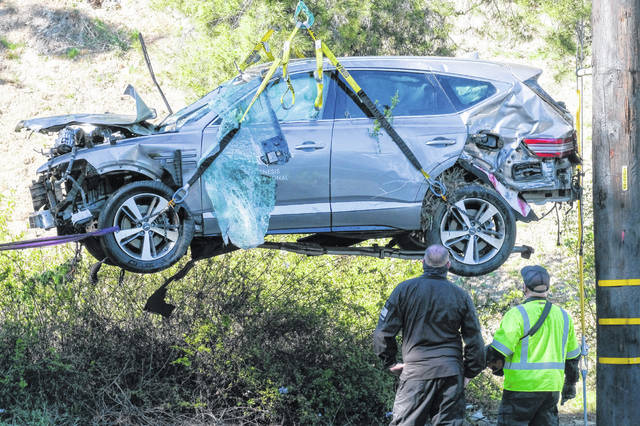 A crane is used Feb. 23 to lift a vehicle following a rollover accident involving golfer Tiger Woods, in the Rancho Palos Verdes suburb of Los Angeles. Authorities said Wednesday that Woods was speeding when he crashed, leaving him seriously injured.