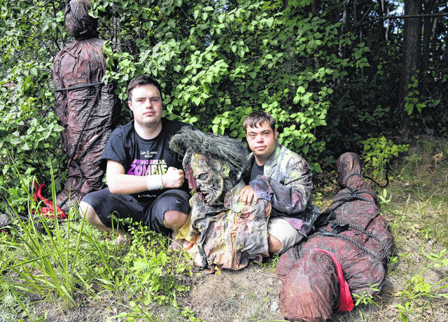 "Sam Suchmann, left, and Mattie Zufelt pose with ghoulish figures July 12, 2016, at Sam's home in Providence, R.I. The two young men who caused a sensation four years ago when they created their own gory zombie movie are back, this time in a documentary championed by a Hollywood luminary that chronicles their tenacious, years-long effort to see their silver screen dream come to fruition. ""Sam & Mattie Make a Zombie Movie,"" was released April 6, on Apple TV."