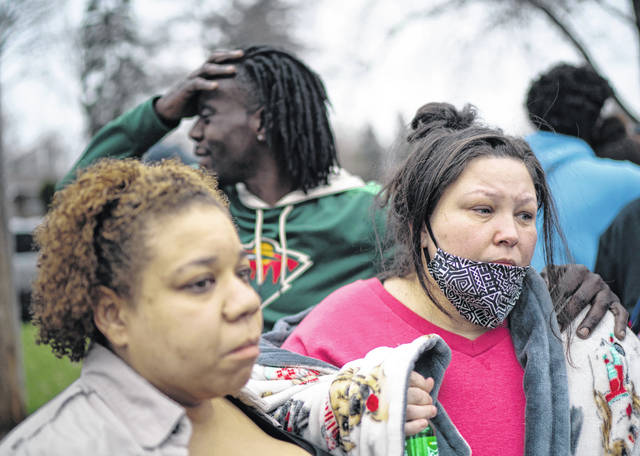 Friends and family comfort Katie Wright, right, while she speaks briefly to news media Monday near where the family says her son Daunte Wright, 20, was shot and killed by police.