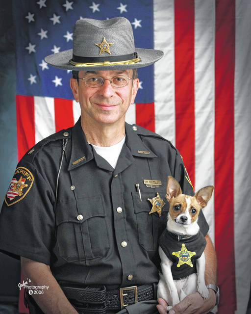 Sheriff Dan McClelland and his small police dog Midge are shown in 2006 at the Geauga County, Ohio, sheriff's department. Both died on April 14. McClelland, died after a lengthy battle with cancer and Midge, perhaps, of a broken heart. The family said they will be buried together. McClelland retired in 2016, after 13 years as sheriff, and 44 total in the department. The last ten with Midge, a drug-sniffing Chihuahua-rat terrier mix certified by Guinness World Records as the smallest police dog on the globe.