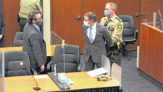 Former Minneapolis police Officer Derek Chauvin, center, is taken into custody Tuesday as his attorney, Eric Nelson, left, looks on.