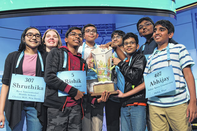 The eight co-champions of the 2019 Scripps National Spelling Bee, from left, Shruthika Padhy, 13, of Cherry Hill, N.J., Erin Howard, 14, of Huntsville, Ala., Rishik Gandhasri, 13, of San Jose, Calif., Christopher Serrao, 13, of Whitehouse Station, N.J., Saketh Sundar, 13, of Clarksville, Md., Sohum Sukhatankar, 13, of Dallas, Texas, Rohan Raja, 13, of Irving, Texas, and Abhijay Kodali, 12, of Flower Mound, Texas, hold the trophy at the end of the competition May 31, 2019, in Oxon Hill, Md. The Scripps National Spelling Bee is undergoing a major overhaul to ensure it can identify a single champion, adding vocabulary questions and a lightning-round tiebreaker to this year's pandemic-altered competition Friday, April 23.