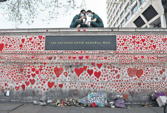 Nurses from the nearby St. Thomas' hospital sit atop the National Covid Memorial Wall in London on Tuesday. Here in the United States, vaccinated people can be without masks outdoors after a change by the CDC.