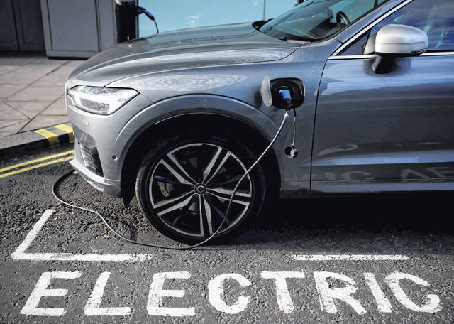 A charging cable is plugged into a Volvo electric vehicle Nov. 18, 2020, in a parking bay reserved for electric vehicles in London.