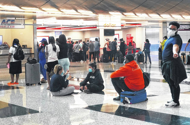 People wait in line at the Miami International Airport Car Rental Center on April 12 in Miami, Florida. Customers are finding that car rental agencies have limited or no supply of vehicles as people begin traveling again after being locked down during the pandemic.