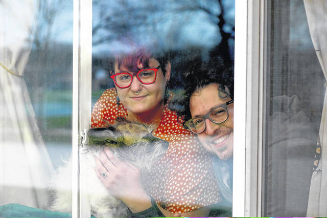 Mo Hoelker, left, and Sam Hoelker, along with their dog Gidget, 11, are seein in a window of their home April 5 in Mount Prospect, Ill. The couple recently purchased their home under the Illinois Housing Development Authority's SmartBuy program.