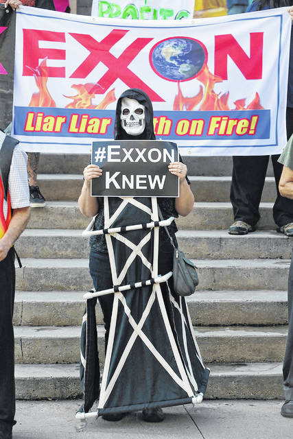 A protester stands outside an Exxon shareholders meeting in Dallas on May 31, 2017. Connecticut sued ExxonMobil Corp. In March, the Securities and Exchange Commission invited public comments on updating the agency's rules for what climate risk information companies should have to let investors know about.