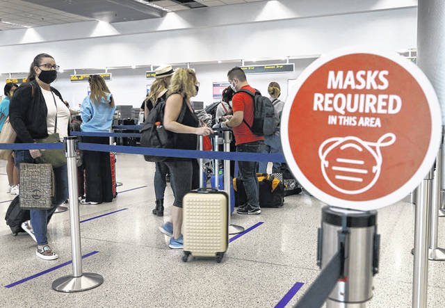 "A sign reading ""masks required in this area"" is seen Feb. 1 as travelers prepare to check in for their Delta airlines flight at the Miami International Airport in Miami."