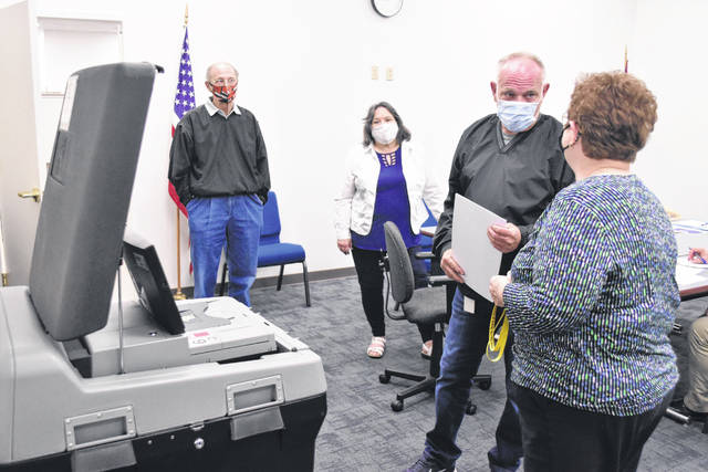 Kathy Meyer, director of the Allen County Board of Elections, shows board members Keith Cheney, Gary Frueh and Mona Willamowski how to run and test voting machines that will be in use during the May 5 election this year.