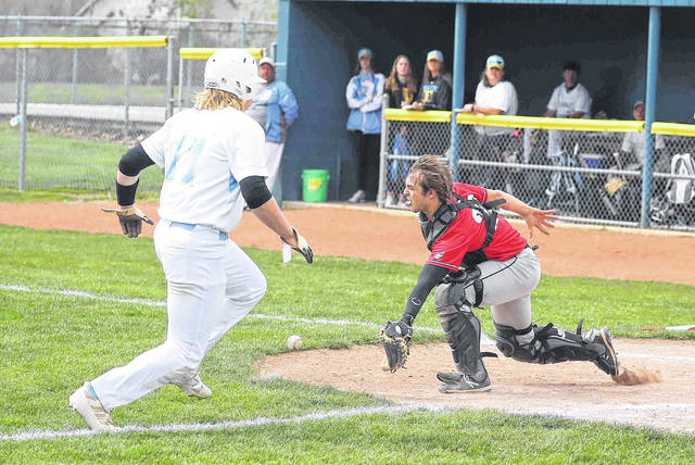 Bath's Lex Boedicker heads to home plate to post a run as Delphos Jefferson's Jacob Simmons awaits the throw during Saturday's game at Bath. See more game photos at LimaScores.com.