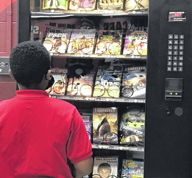 JayQuan Ackles peruses Heritage Elementary School's book vending machine on Friday. Ackles was the first student to use the vending machine, which allows students to earn a book of their own for good behavior.
