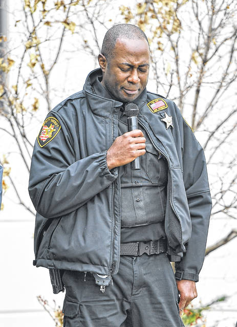 Deputy Damian Tibbs says a prayer during Thursday's flag-raising at Allen County Children Services to kick off Child Abuse Prevention Month.