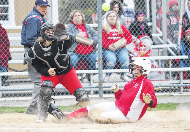 Lima Central Catholic's Jaylen Roehm slides safe into home as Delphos Jefferson's Lillian Baughn awaits the throw during Thursday's game at Delphos Jefferson. See more game photos at LimaScores.com.