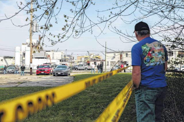 A retired employee of the Yenkin-Majestic Paint company watches as first responders work the scene of an overnight explosion at the facility Thursday in Columbus, Ohio.
