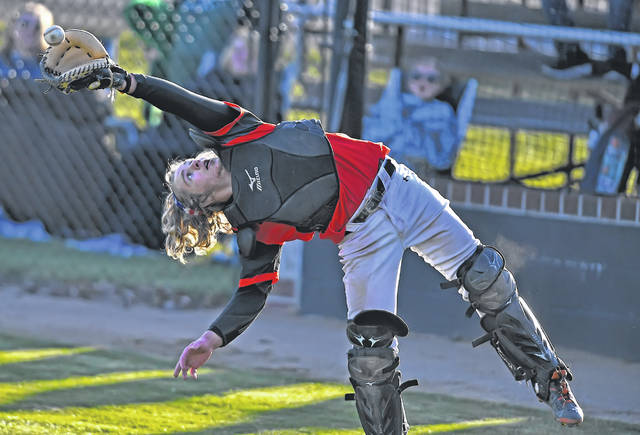 Elida's Mike Niebel catches a pop up during Friday's game against Ottoville at Elida's Ed Sandy Field.