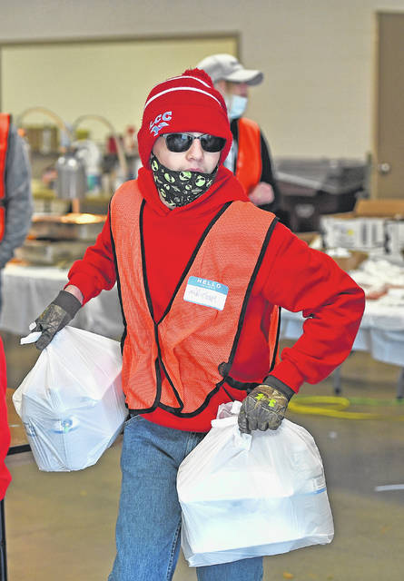 Michael Sherrick, 13, hands out meals Friday at the Ottawa River Coalition Good Friday Fish Fry at the Allen County Fairgrounds. The event was a drive-thru and was catered by Lock 16.