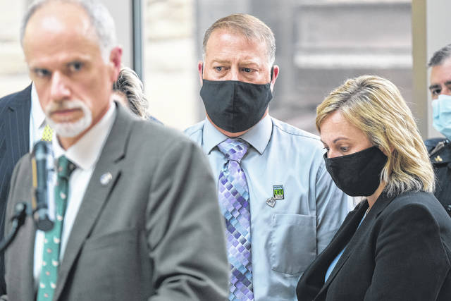 Cory and Shari Foltz, the parents of a Bowling Green State University student Stone Foltz, who died in an alleged hazing incident, look on while Wood County Prosecutor Paul Dobson, left, takes questions from the media Thursday afternoon at the Wood County Courthouse.