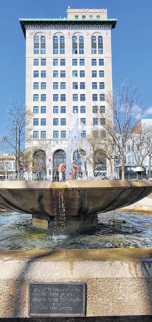 The fountain near the intersection of Main and Market streets in downtown Lima shoots upward with 43 Town Square in the background. Warmer weather led to removing the cover of the fountain recently and letting the water flow.