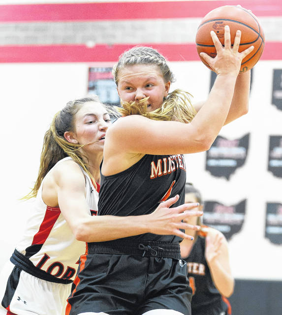 Minster senior guard Ivy Wolf drives to the basket with pressure from Fort Loramie's Kenzie Hoelscher during a regular season match-up earlier this season.