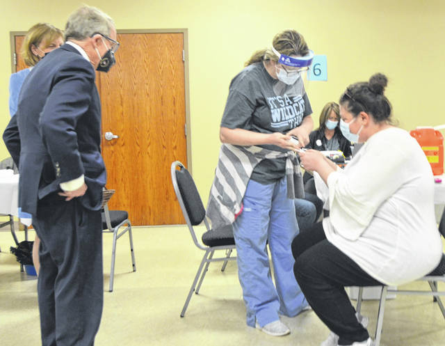 Ohio Gov. Mike DeWine, left, and his wife, Fran, watch as Emily Demasi, right, finishes her vaccine paperwork with Candace Roberts, of Allen County Public Health, during a mass vaccination clinic in Lima.